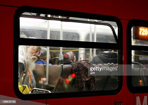 A man aboard a passing public transit bus looks toward a makeshift memorial to Grammywinning pop legend and actress Whitney Houston near the Beverly...