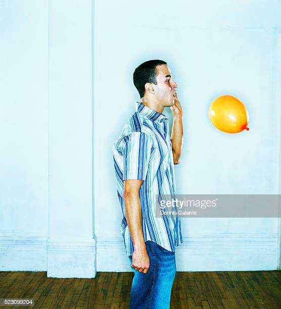 Man About to Hit Yellow Balloon