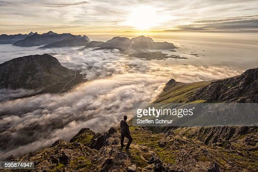 Man above the clouds on mountain Lofoten Norway : Stock Photo