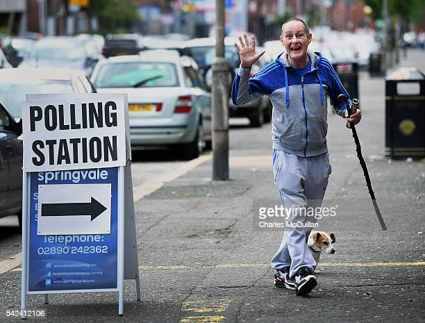 A man accompanied by his dog waves as he makes his way into a polling station to vote in the EU referendum on June 23 2016 in Belfast Northern...