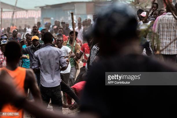 A man accused of being from the Kikuyu ethnic group by a group of Kenyans belonging to the Luo tribe falls down as he is beaten with a wooden rod by...