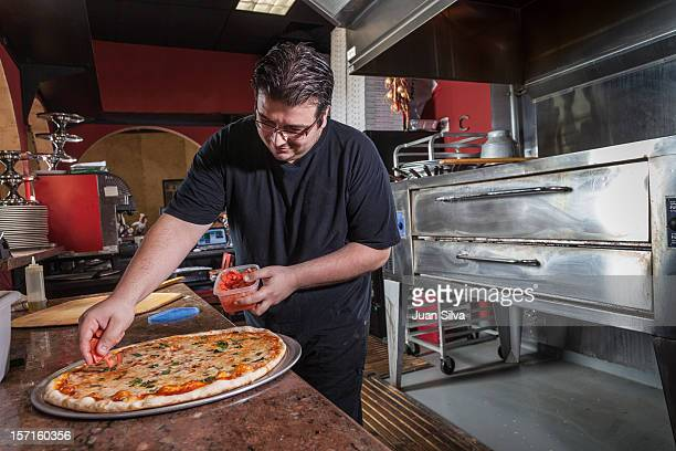 Man adding fresh tomatoes to pizza in a restaurant