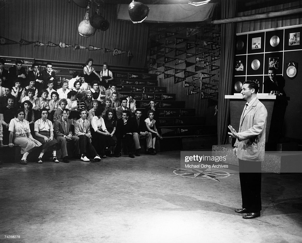 A man addresses a crowd of kids sitting on mock bleachers as host of the television show 'American Bandstand' Dick Clark looks on in circa 1958