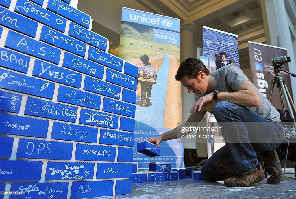 A man adds a brick made of Lego blocks to a wall as pupils and volunteers attempt to build the world's longest Lego wall at the Palais des Beaux-Arts in Brussels (BOZAR) on January 10, 2014. The event takes place until January 11 to support a UNICEF campaign to raise awareness about the need to construct new schools in developing countries. AFP PHOTO / GEORGES GOBET