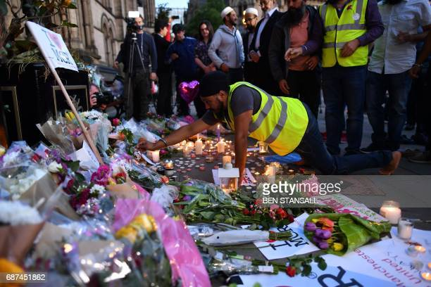 A man adds a single rose to a mound of messages and floral tributes in Albert Square in Manchester northwest England on May 23 in solidarity with...