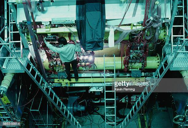 Man Adjusting a Particle Detector