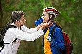 Man adjusting bicycle helmet for woman