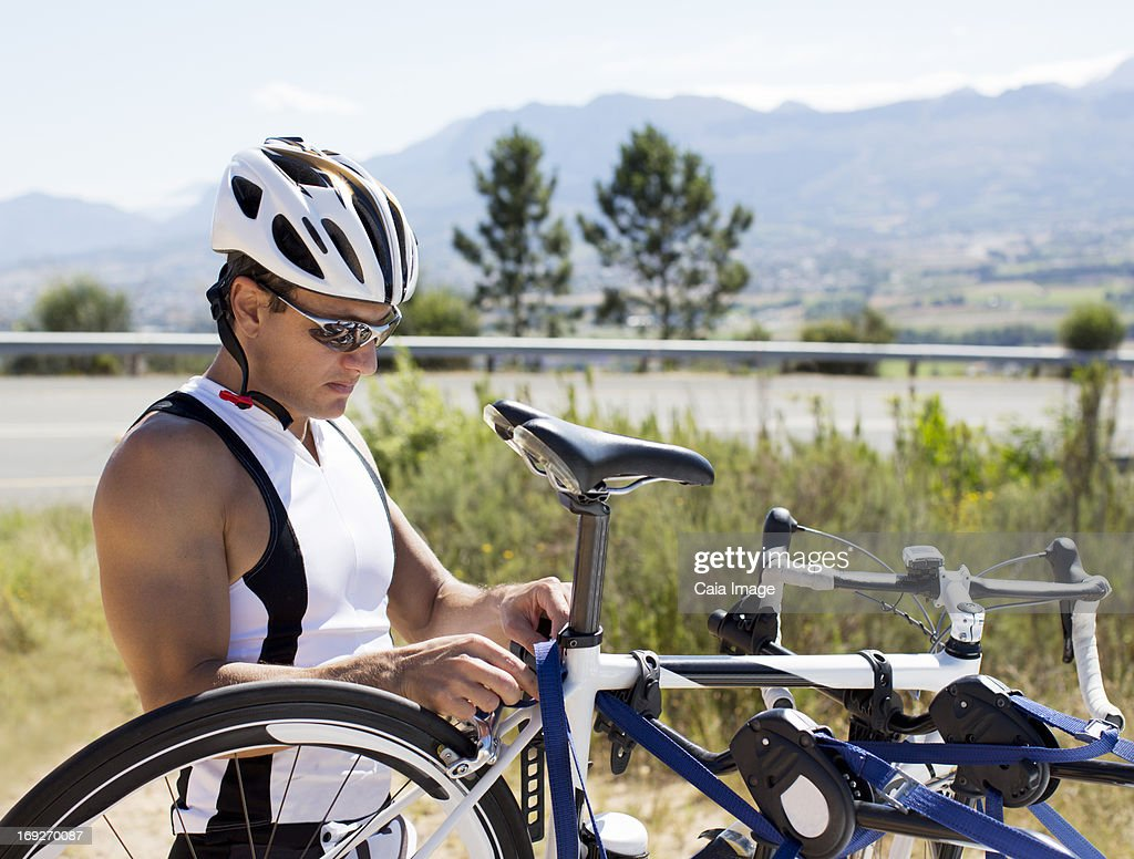 Man adjusting bicycle outdoors : Stock Photo