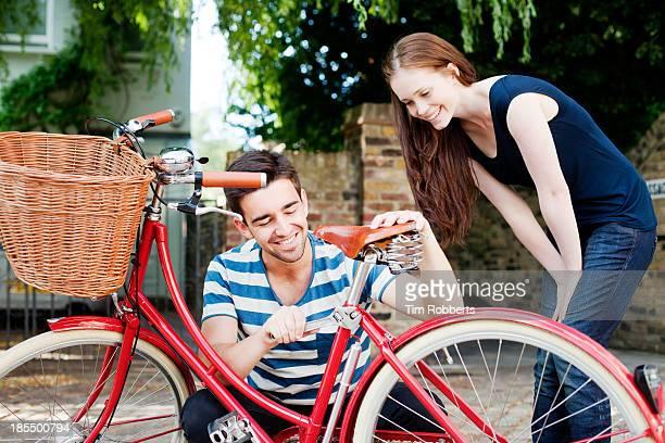 Man adjusting bike with woman