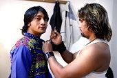 Man adjusting Bollywood actor's costume, waist up