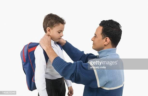 Man adjusting collar of his son