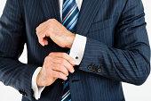 man adjusting cuff links on his suit