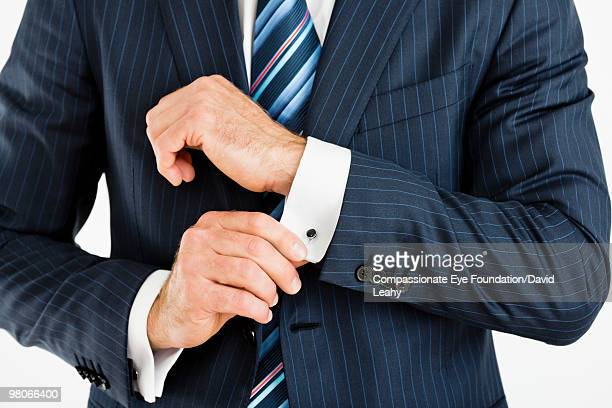 man adjusting cuff links on his suit