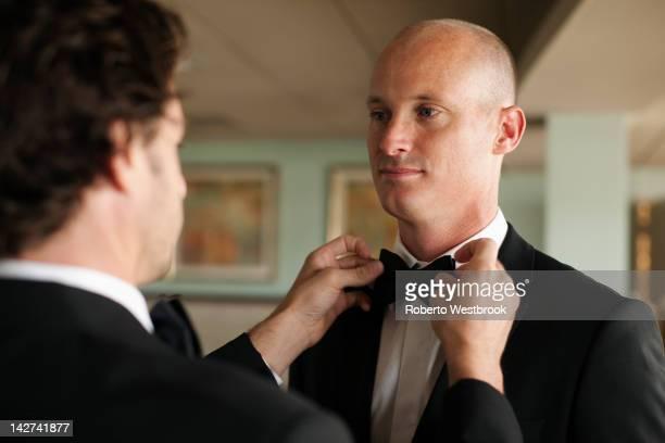 Man adjusting groom's bow tie