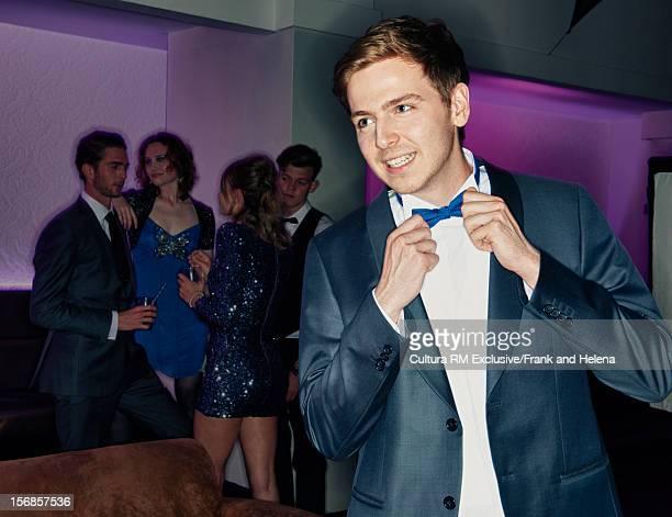 Man adjusting his bow tie in nightclub