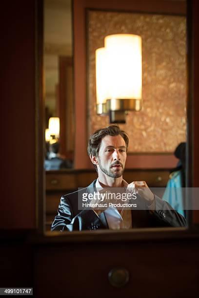 Man adjusting his collar in mirror