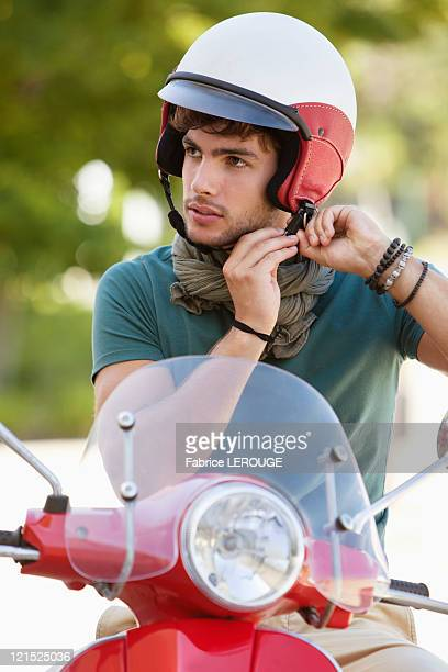 Man adjusting his helmet on a scooter