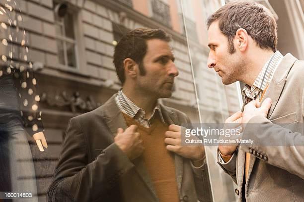 Man adjusting his suit in window
