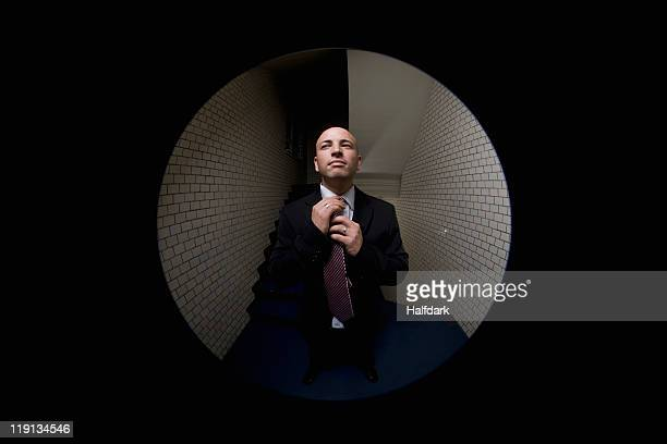 A man adjusting his tie, viewed through a peephole