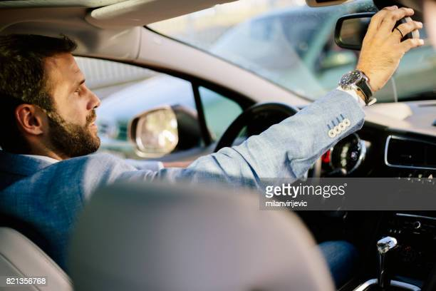 Man adjusting rearview mirror in the car