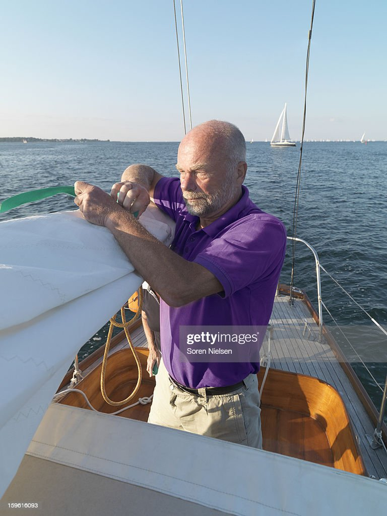 Man adjusting rigging on sailboat : Stock Photo