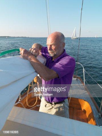 Man adjusting rigging on sailboat : Stock Photo