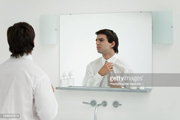 Man adjusting shirt collar in mirror