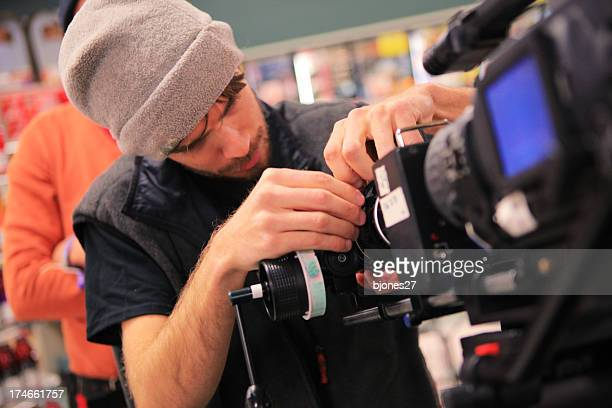 A man adjusting the settings on a camera