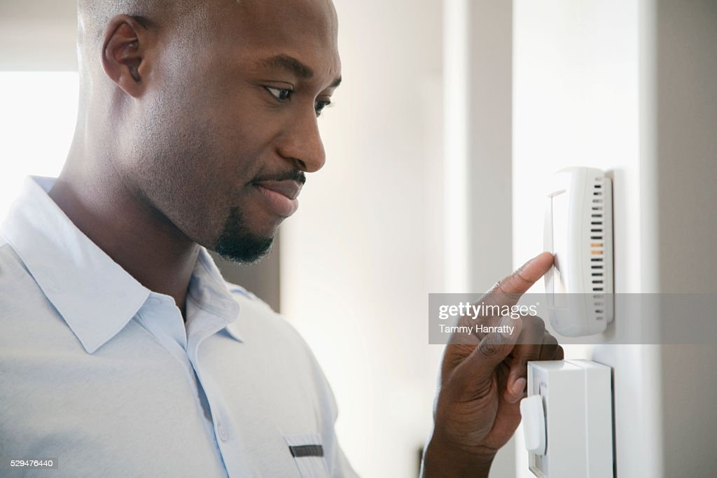 Man adjusting thermostat : Stock Photo