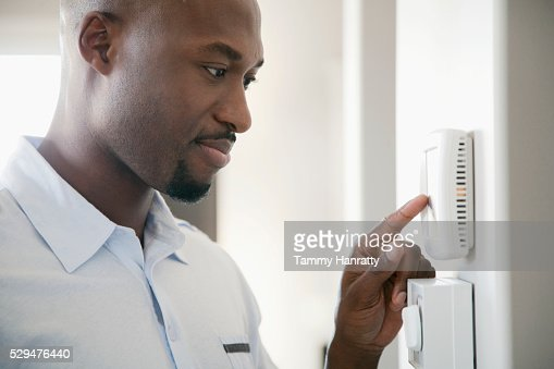 Man adjusting thermostat : Foto de stock