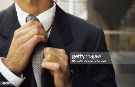 Man adjusting tie, cropped