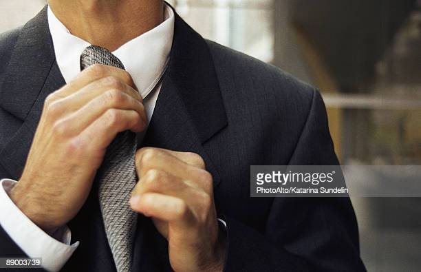 Man adjusting tie, cropped