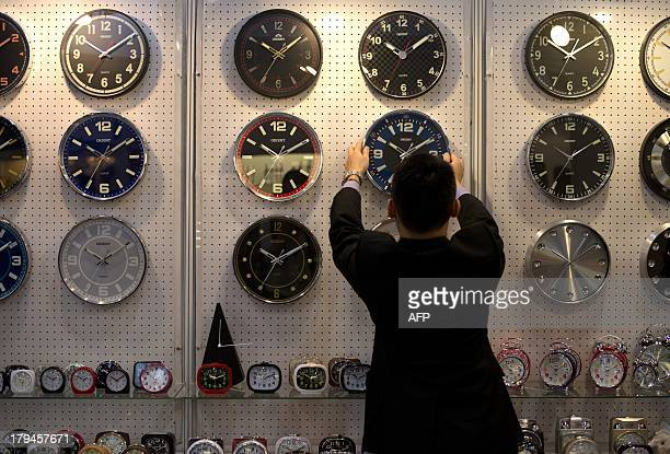 A man adjusts a clock on display at the Hong Kong Watch and Clock Fair the largest fair of its kind in the world on September 4 2013 The fair which...