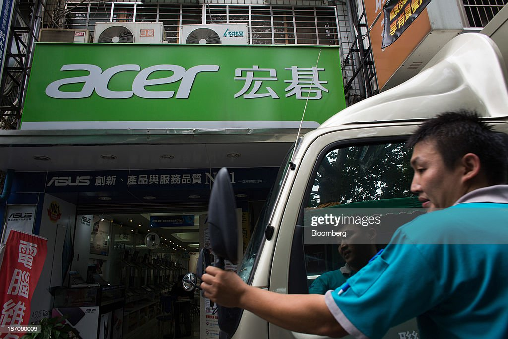 A man adjusts a rear view mirror on a truck in front of Acer Inc. signage displayed outside an electronics store on Bade Road in Taipei, Taiwan, on Wednesday, Nov. 6, 2013. Acer, Taiwans second-largest computer maker, plunged to a 12-year low in Taipei trading after announcing a record loss, job cuts and the resignation of J.T. Wang as chief executive officer. Photographer: Lam Yik Fei/Bloomberg via Getty Images