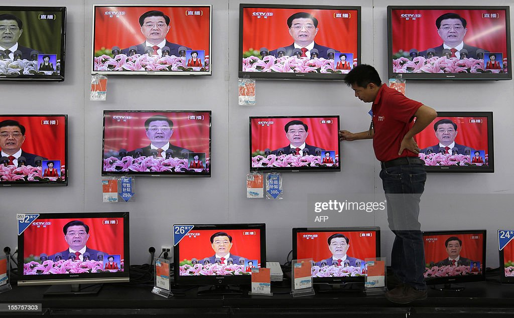 A man adjusts a television screen showing a live broadcast of Chinese president Hu Jintao speaking at the opening of the 18th Communist Party Congress, at a supermarket in Wuhan, central China's Hubei province on 8 November 2012. Vice President Xi Jinping had moved closer to taking the reins of power and is expected to replace President Hu Jintao as party chief in a once-a-decade power transition, setting the stage for his promotion to president of the world's most populous nation, expected by March 2013. CHINA
