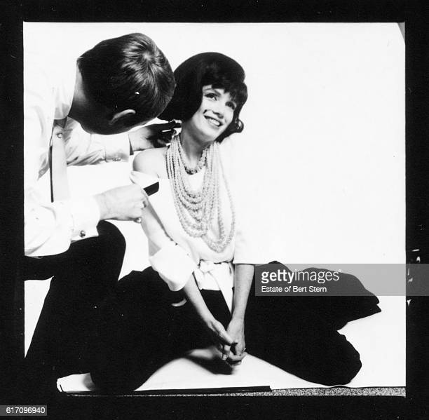 A man adjusts a wig worn by American actress Marilyn Monroe during a photoshoot in Beverly Hills California July 1962 The two sessions for the...