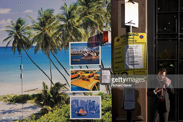 A man adjusts his mp3 player with the hoarding of a travel business's construction site showing a tropical beach paradise and images of world cities...