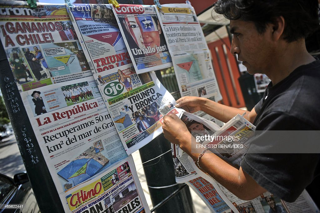 A man adjusts his newsstand in Lima, on January 28, 2014. Newspapers are highlighting the result of the ruling of the International Court of the Hague on a maritime dispute between Peru and Chile. Lima cried victory Monday after the UN's top court handed it a wedge of sea under Chilean sovereignty, but Peruvian fishermen nevertheless said they gained nothing from the historic ruling. AFP PHOTO/ERNESTO BENAVIDES