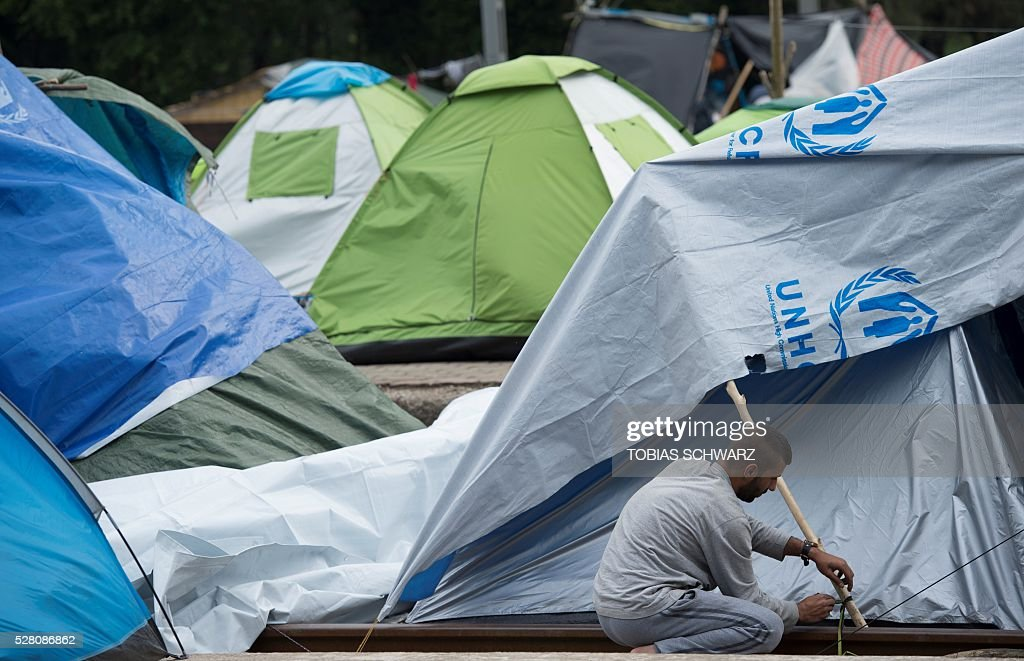 A man adjusts his tent at a makeshift camp for migrants and refugees near the village of Idomeni not far from the Greek-Macedonian border on May 4, 2016. Some 54,000 people, many of them fleeing the war in Syria, have been stranded on Greek territory since the closure of the migrant route through the Balkans in February. / AFP / TOBIAS