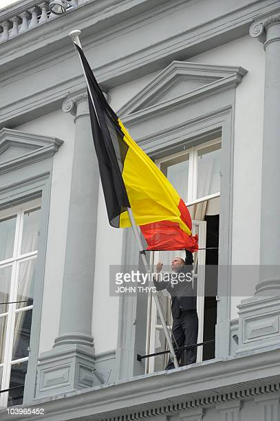 A man adjusts the Belgium flag before the Foreign Affairs Ministers meeting on September 10 2010 at the Egdmont palace in Brussels AFP PHOTO / JOHN...