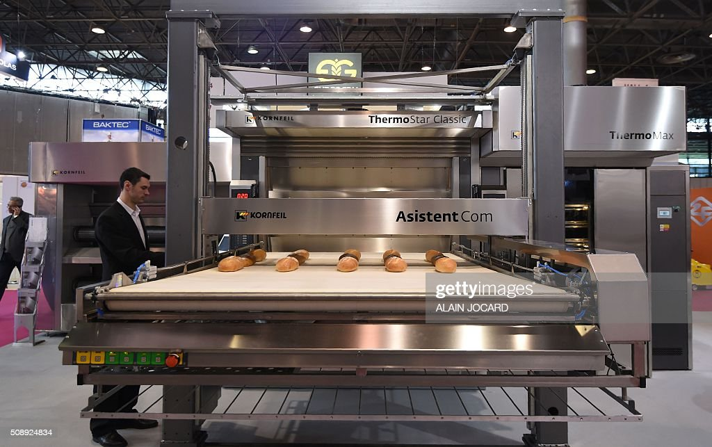 A man adjusts the settings of a machine on display at the stand of Czech bakery oven manufacturer Kornfeil at the 'Europain' fair in Villepinte near Paris on February 7, 2016. / AFP / ALAIN JOCARD