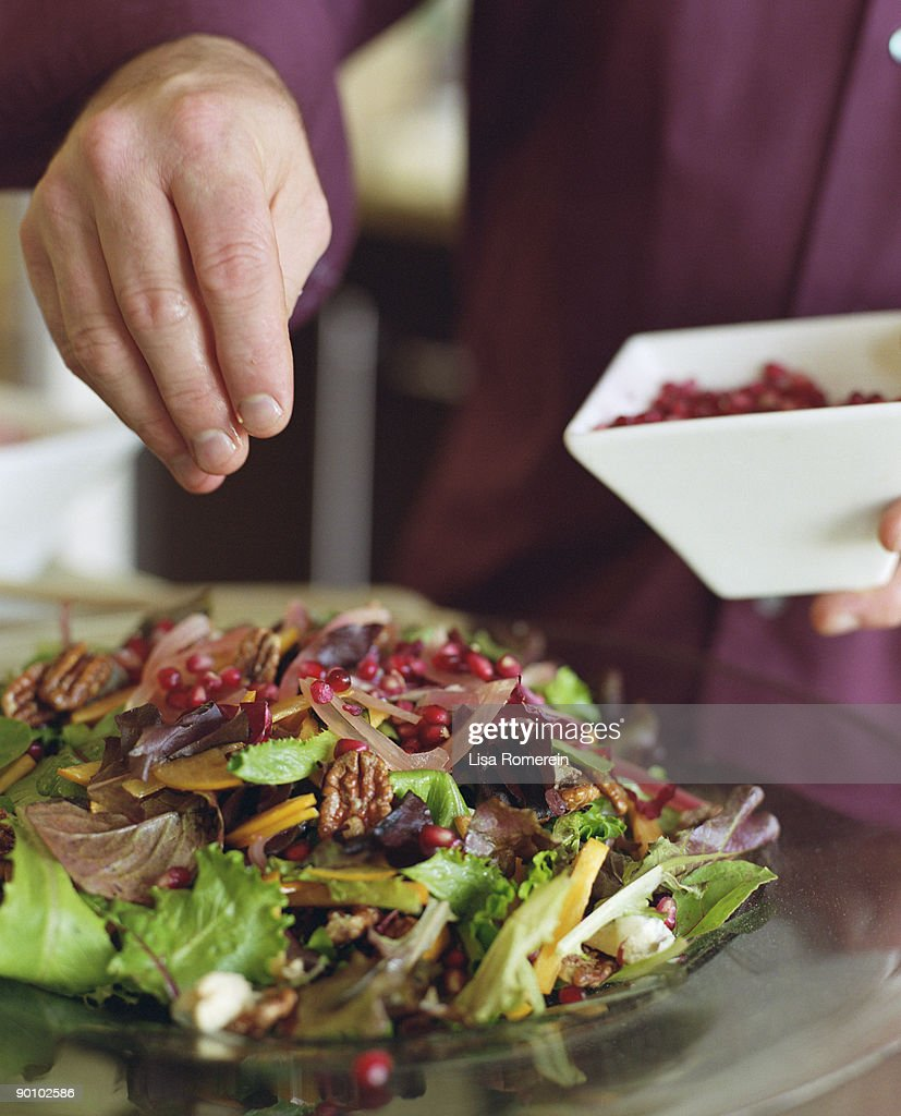 Man adorning salad with pomegranate seeds