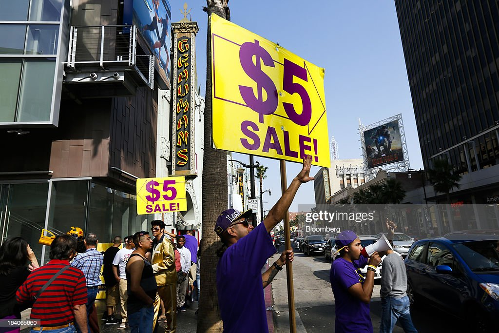 A man advertises a 'Five-Dollar Sale' to tourists on Hollywood Boulevard near the Chinese Theatre in (Hollywood) Los Angeles, California, U.S., on Saturday, March 16, 2013. California should start a state-run bank to finance economic development that's less polluting and more environmentally friendly, financed by auctions of greenhouse-gas carbon credits, Lieutenant Governor Gavin Newsom said. Photographer: Patrick T. Fallon/Bloomberg via Getty Images