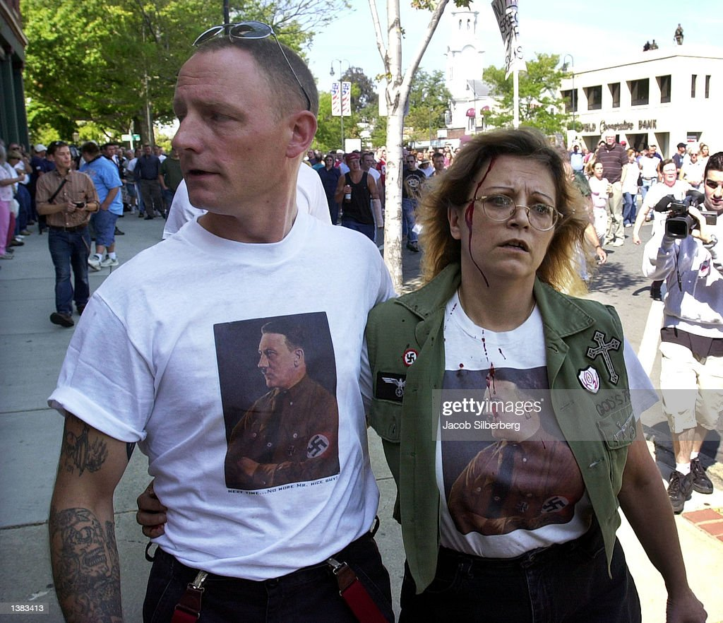 A man affliiated with the neoNazi leads helps a women away from a crowd of protesters chasing them outside the Wakefield Town of Beebe Public Library...