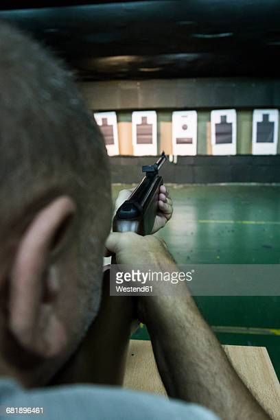Man aiming and calibrating a carbine in an indoor shooting range