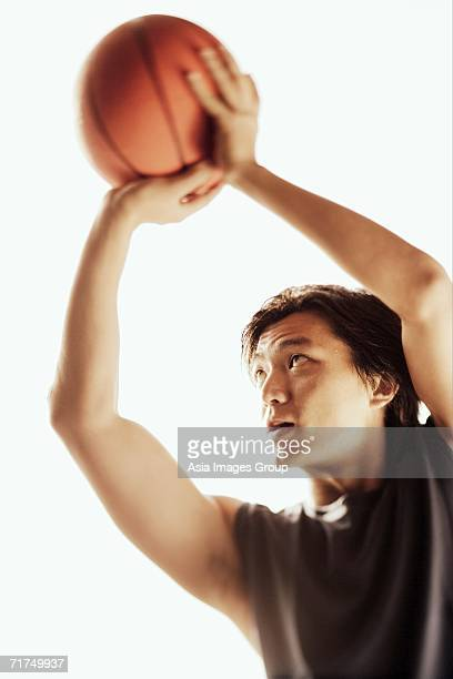 Man aiming basketball, looking away