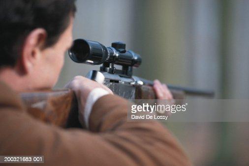 Man aiming rifle, close-up, rear view