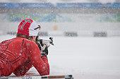 Man aims biathlon rifle at target