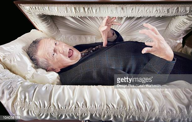 A Man Alive And Laying In A Coffin