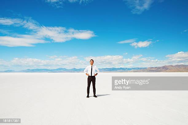 Man alone in salt flats, looking up smiling.